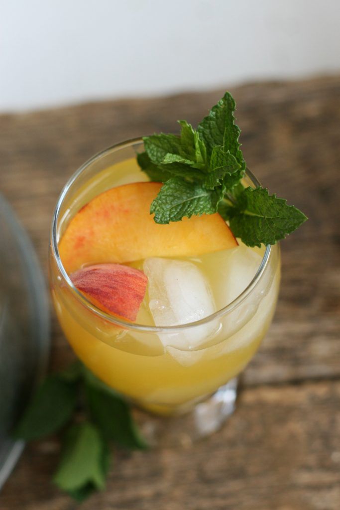 Clear footed glass with summer sangria, ice cubes, fresh peach slices, and a sprig of fresh mint sitting on reclaimed wood boards