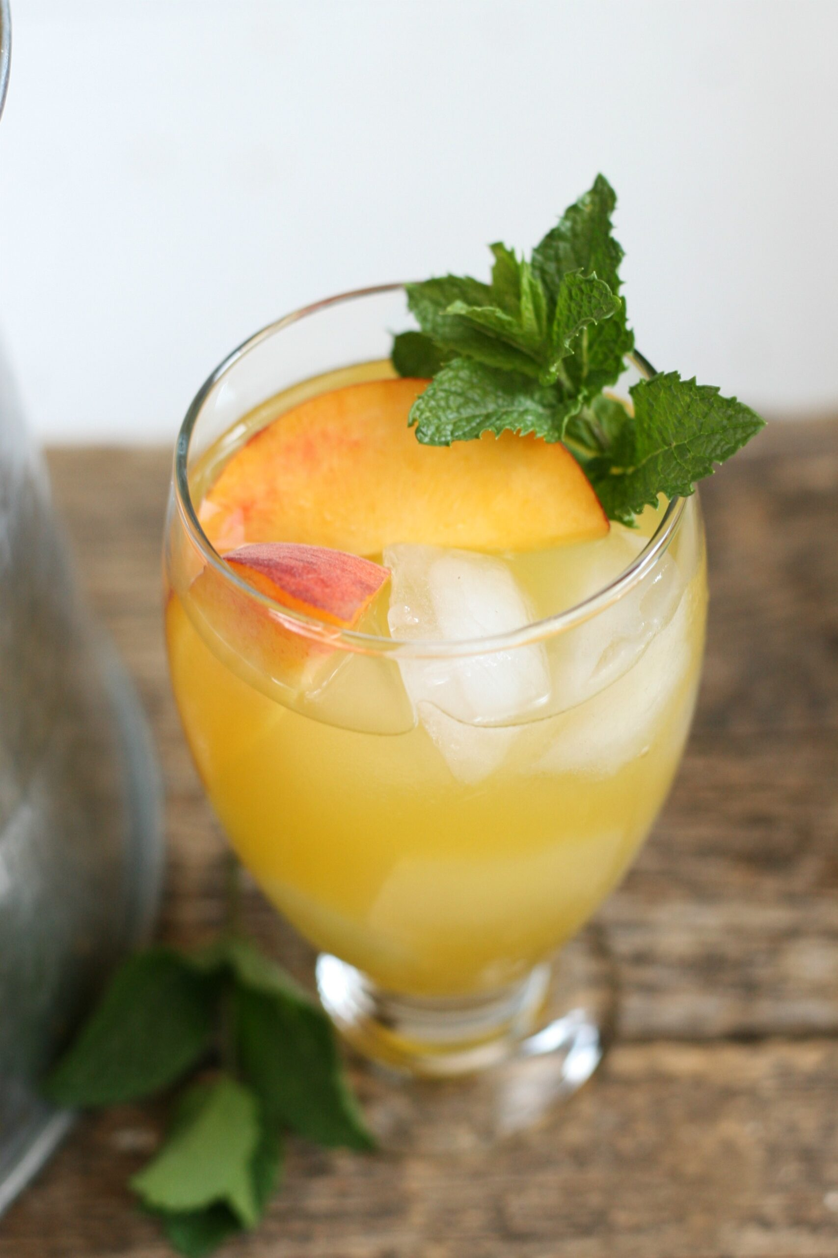 Summer sangria in clear footed glass with fresh peach slices, ice cubes, and a piece of fresh mint