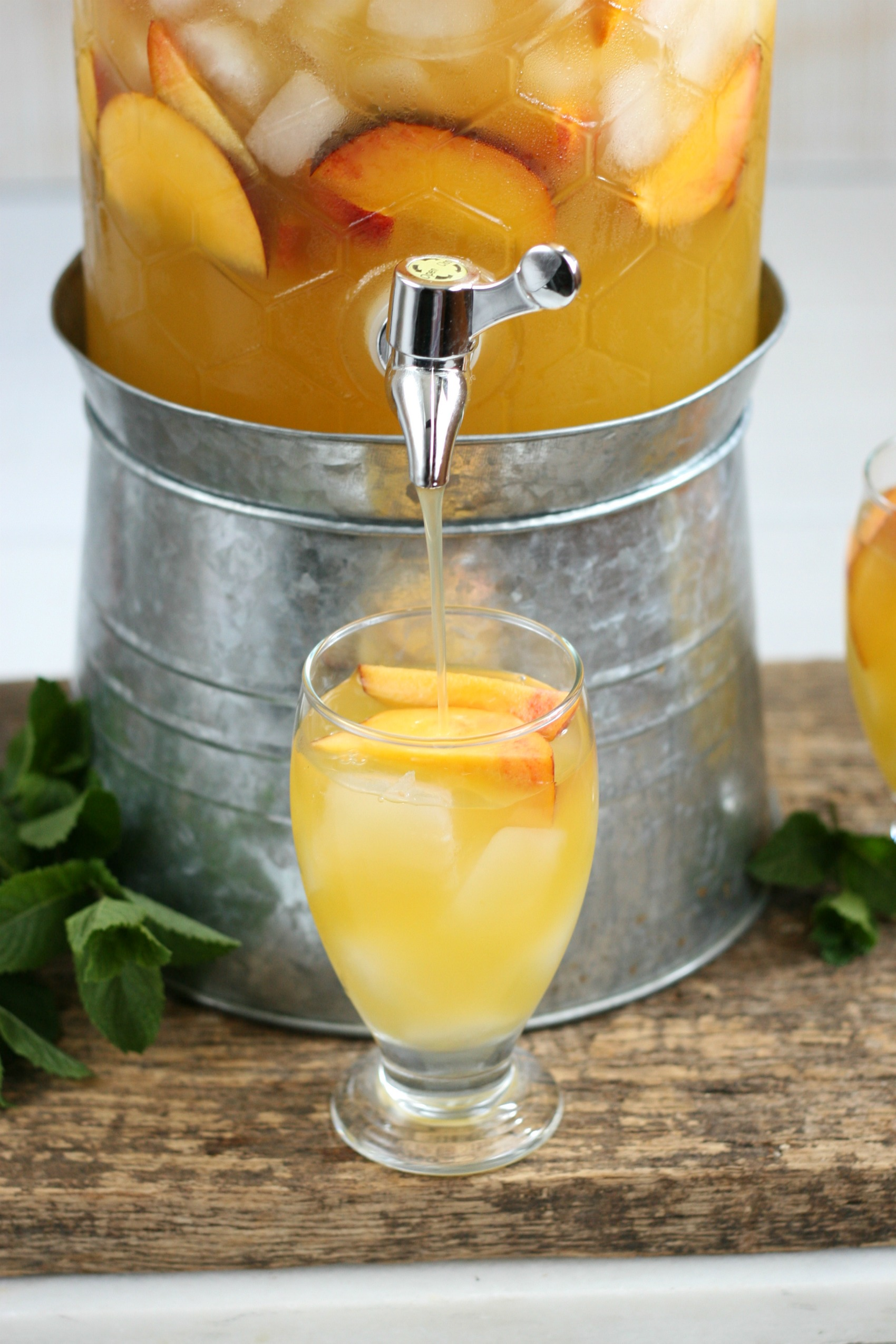 Summer sangria pouring out of a clear glass drink dispenser into a footed glass with ice cubes and slices of peaches.