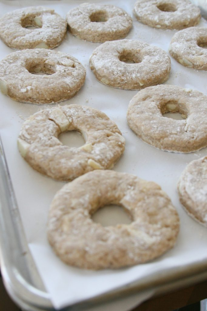apple cider doughnuts on a sheet pan before frying