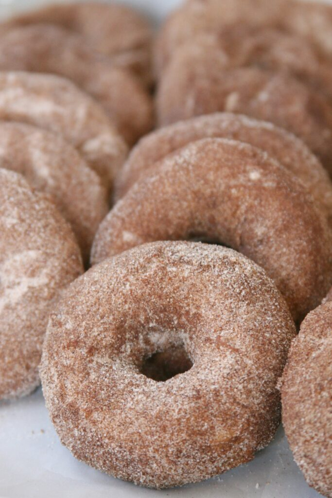 Apple Cider Doughnuts sprinkled with cinnamon sugar, leaning against each other on baking sheet pan