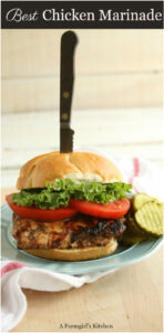 grilled chicken sandwich with heirloom tomato slices and green leaf lettuce with a knife in the bun