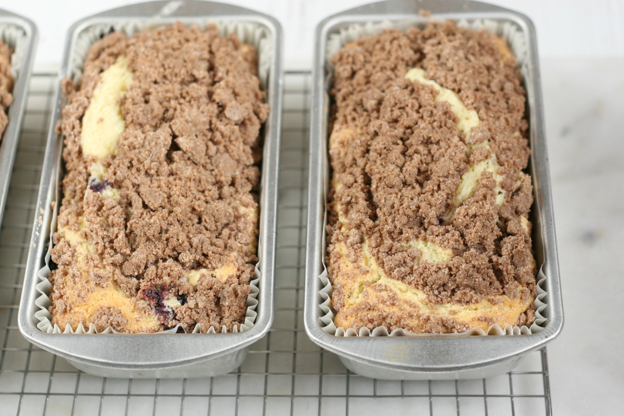 Blueberry Peach Coffee cakes in loaf pans cooling on a baking rack.