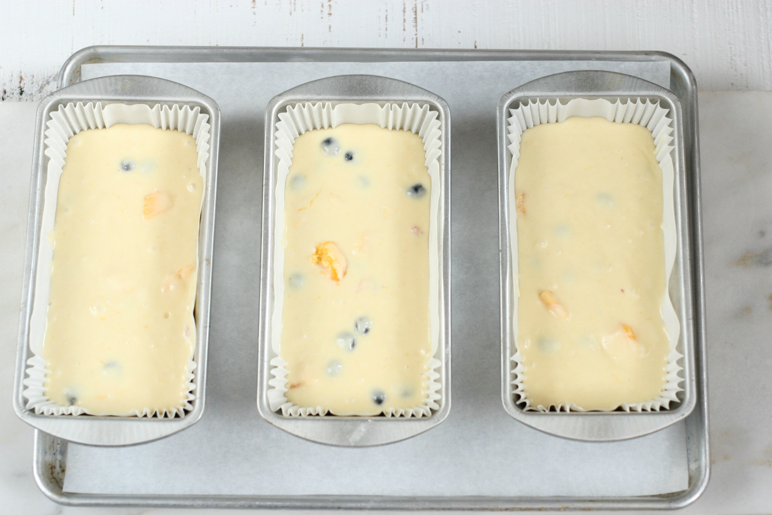 coffee cake batter in three loaf pans sitting on a half sheet pan lined with parchment paper.