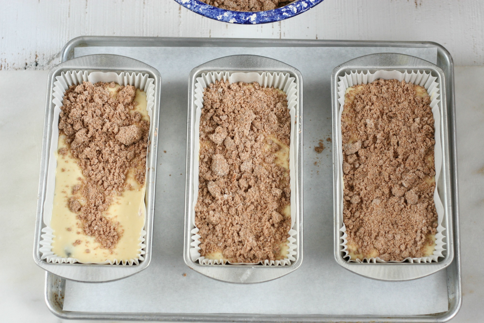 streusel topping being spooned onto coffee cake batter in loaf pans.