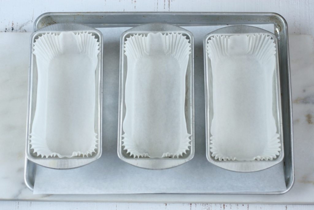 Metal loaf pans sitting on a half sheet pan lined with paper liners