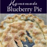 blueberry pie in clear glass pie dish, metal pie server to left