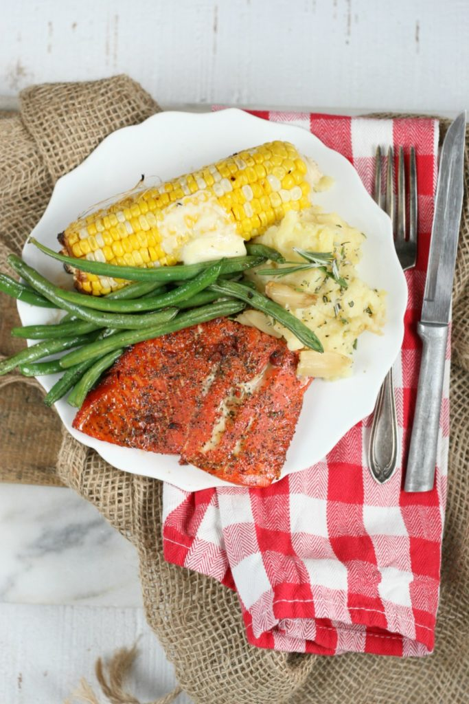 Piece of Wild Salmon with maple bacon spice rub, grilled corn on the cobb, fresh green beans and roasted garlic rosemary mashed potatoes
