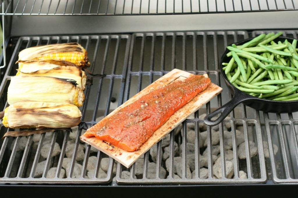 Wild Salmon from The Fresh Market on a maple wood plank on a charcoal grill