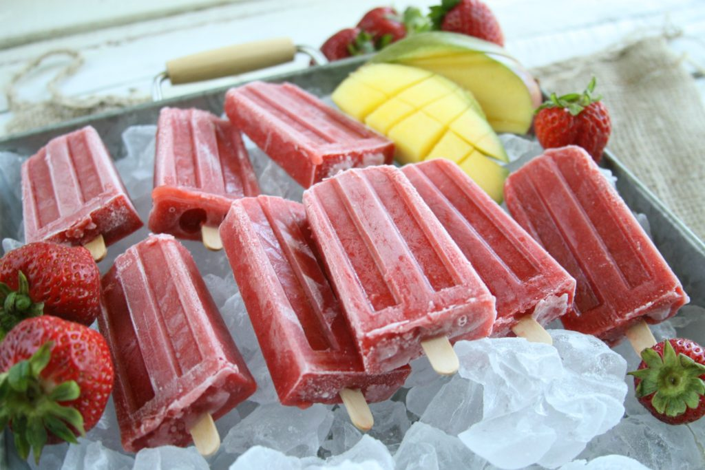Strawberry Mango ice pops sitting in a layer of ice on a galvanized tray