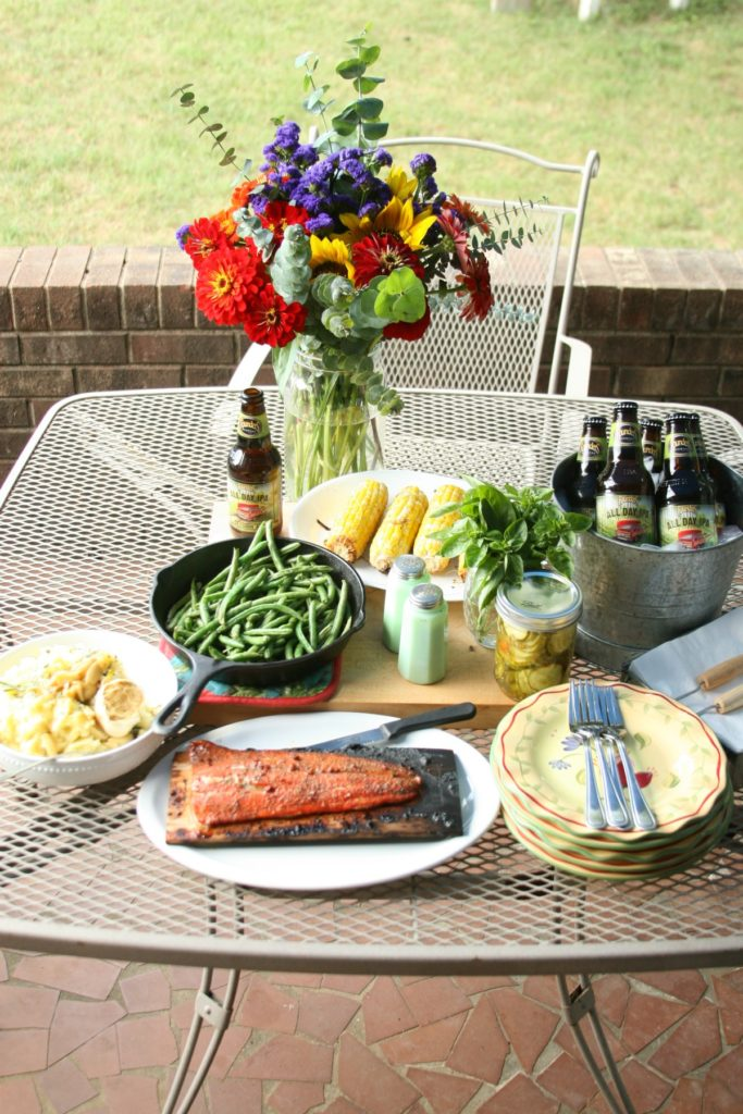 outdoor patio table with full spread of grilled salmon, corn on the cobb, plates, forks, napkins, and flowers in clear vase