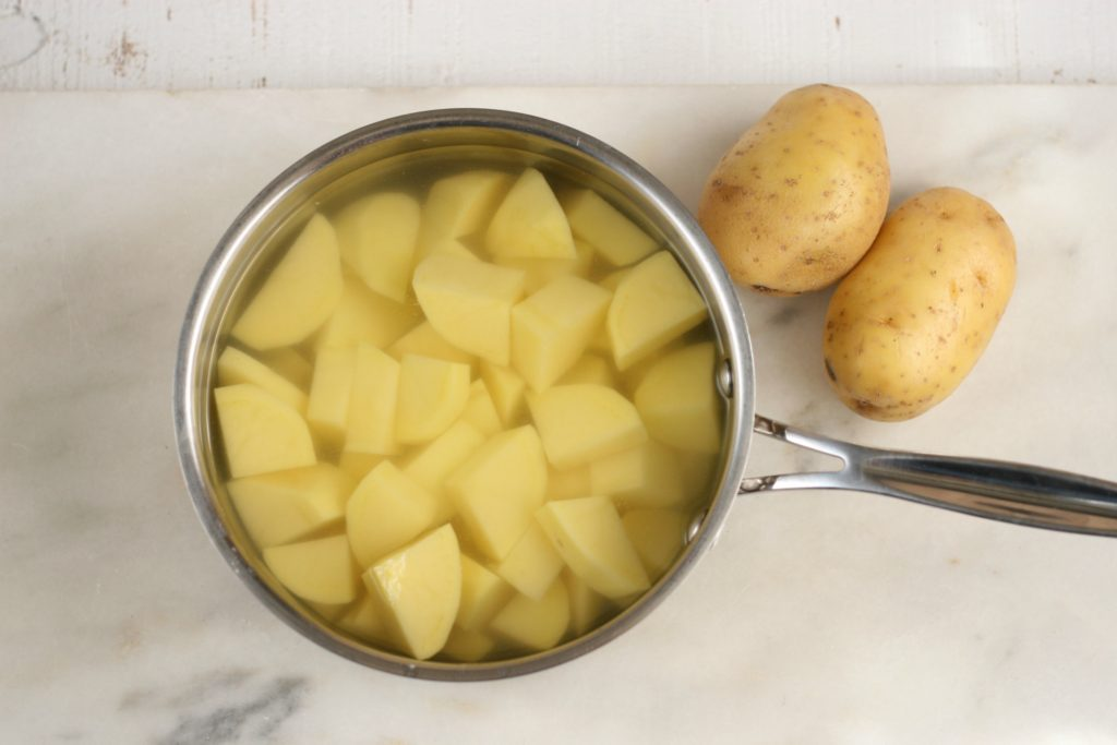 potatoes in saucepan with water and whole potatoes sitting to the right side on a piece of white marble