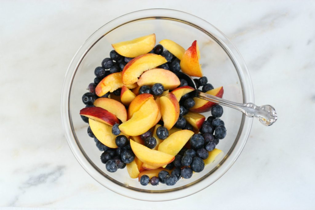 fresh blueberries and peaches in a clear pyrex bowl sitting on white marble