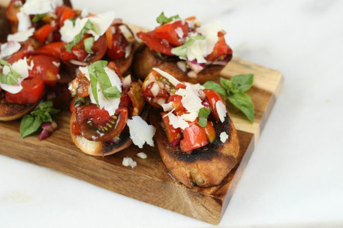 Bruschetta on a wooden cutting board with shaved Parmesan cheese and fresh basil