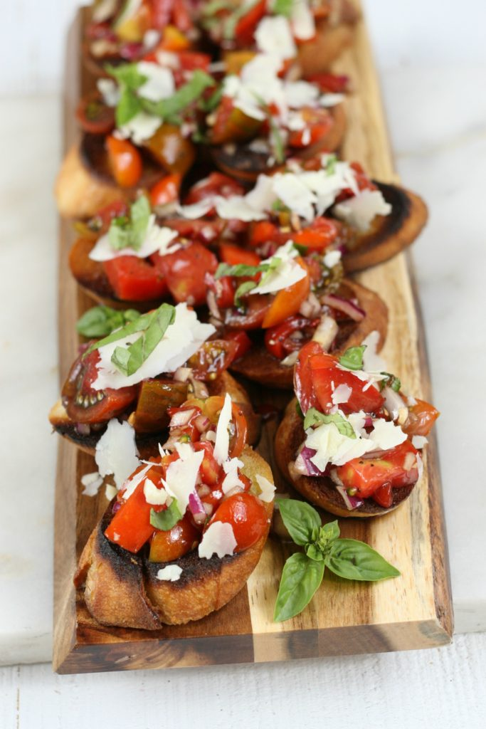 bruschetta on a cutting board with heirloom tomatoes and freshly shaved Parmesan cheese