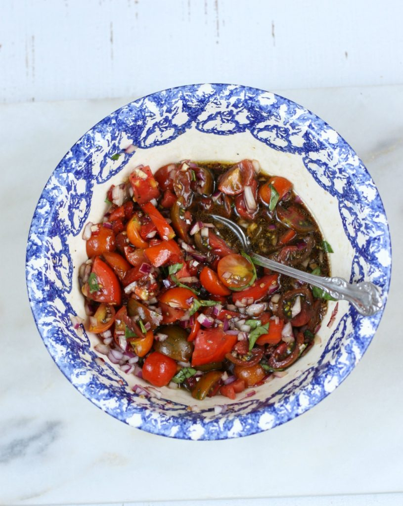 heirloom tomatoes, onions, olive oil, and balsamic vinegar in a blue speckled bowl