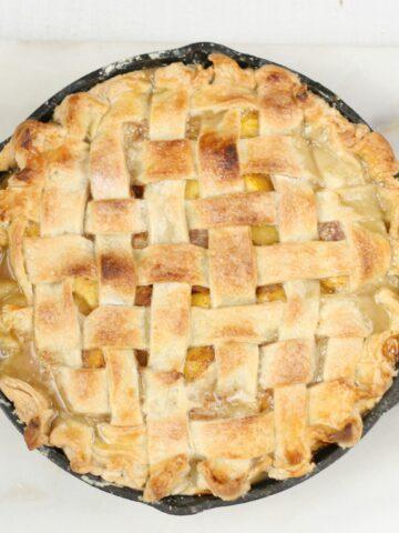 homemade peach pie in 2-handle Lodge cast iron pan