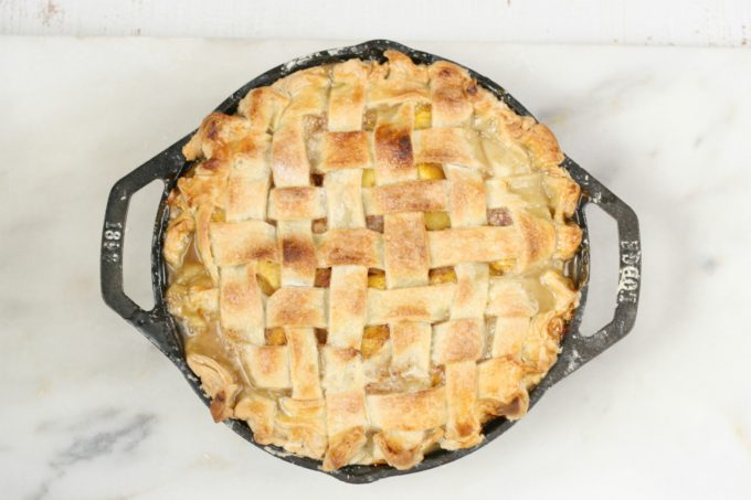 homemade peach pie in 2-handle Lodge cast iron pan