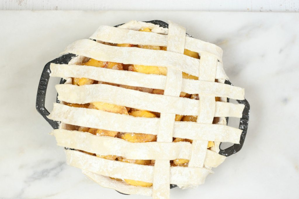 weaving of a lattice crust on a cast iron peach pie