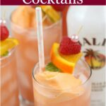 cocktail drinks in clear cylinder glasses with a scoop of orange sherbet, fresh raspberry and slice of orange on top