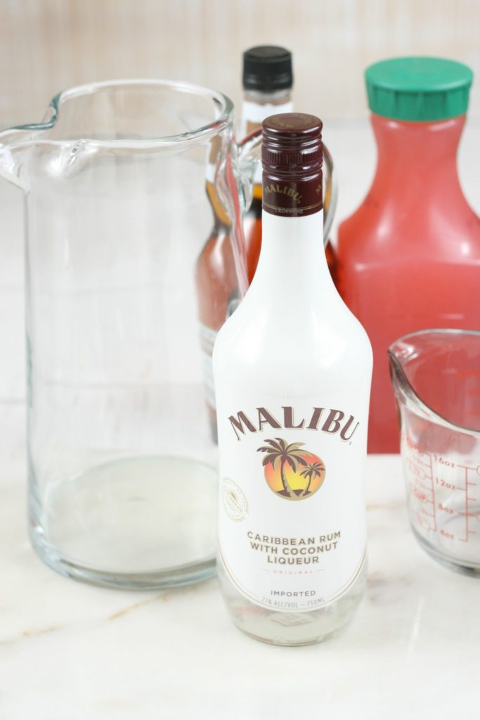 glass pouring pitcher with ingredients set to the side, raspberry lemonade, amaretto, and malibu