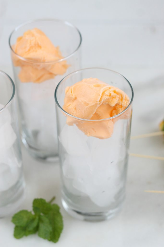 scoops of orange sherbert in cocktail glasses filled with ice