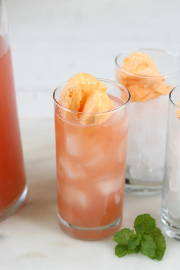 orange sherbet floating in the top of pink bikini cocktails