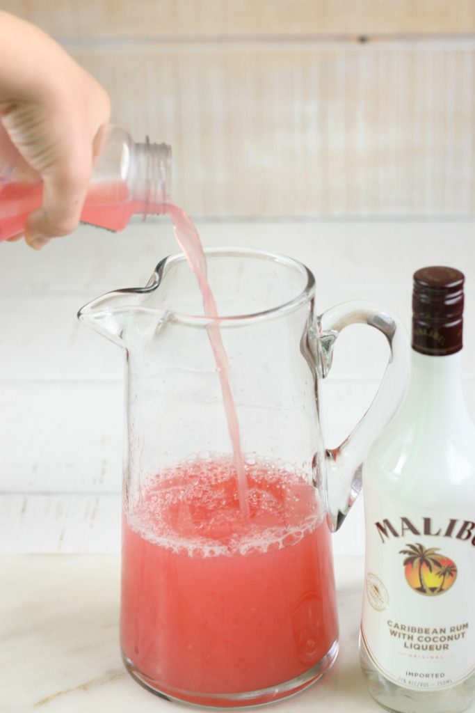 raspberry lemonade being poured into a pouring pitcher with a bottle of malibu on the right