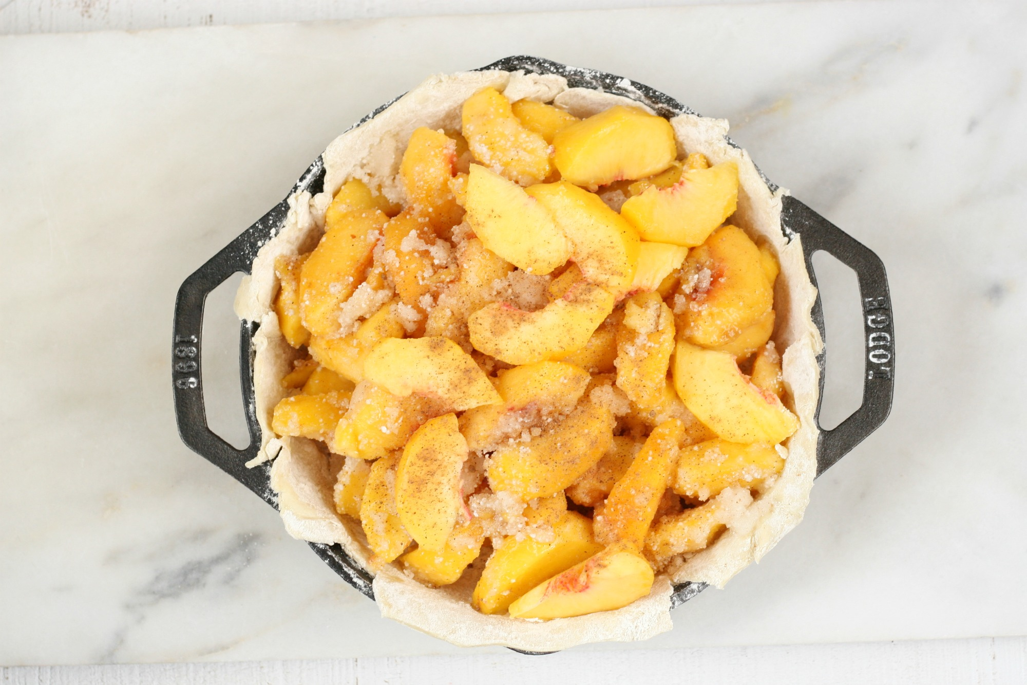 2 handle cast iron pan with peaches in a bottom crust.