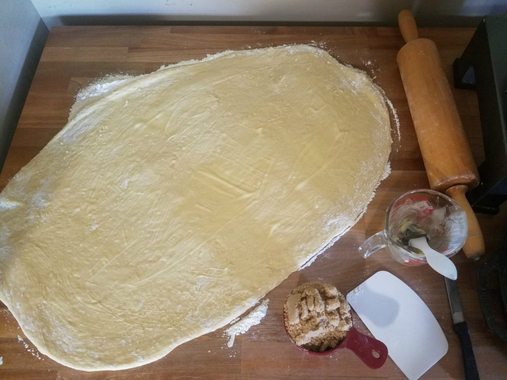 cinnamon roll dough rolled out and melted butter brushed on with a pastry brush