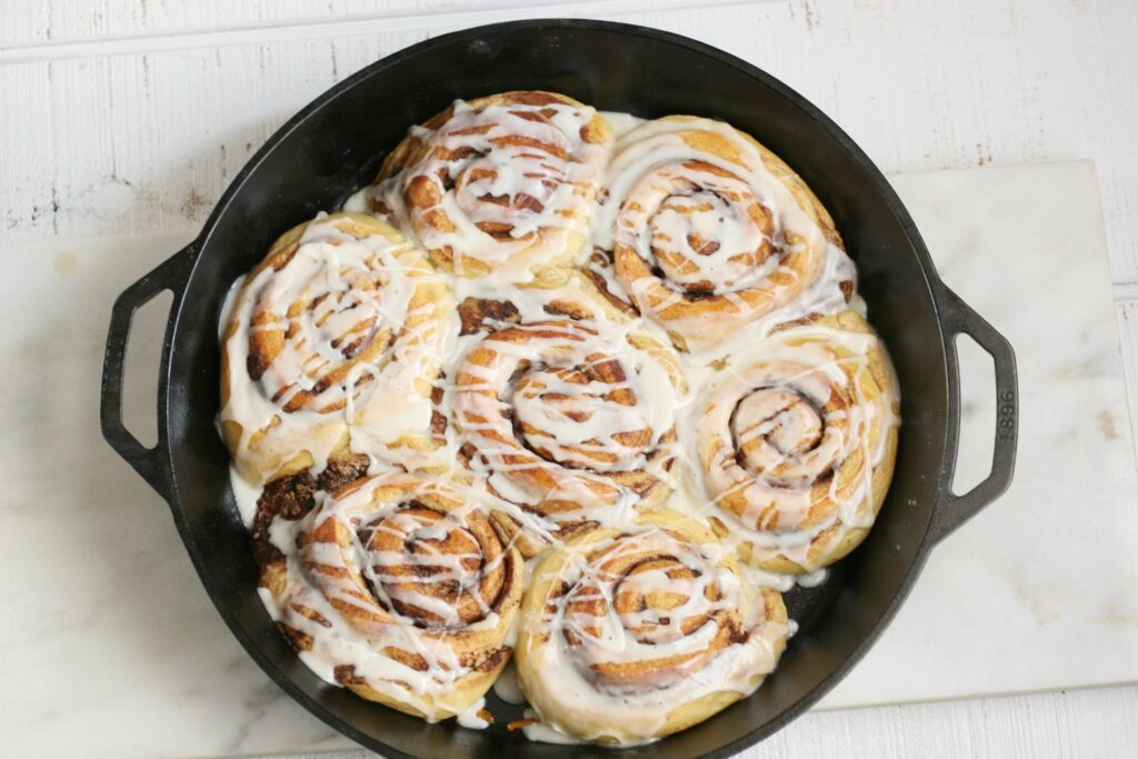 cinnamon rolls in a cast iron pan drizzled with icing
