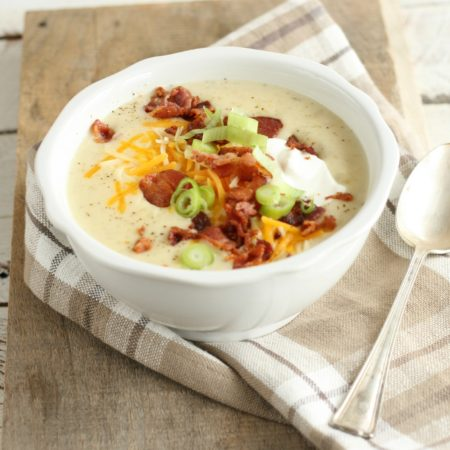 loaded baked potato soup with crumbled bacon pieces, shredded cheddar cheese, sour cream, and thin slices of green onions in a white glass bowl with large spoon to the right of the bowl