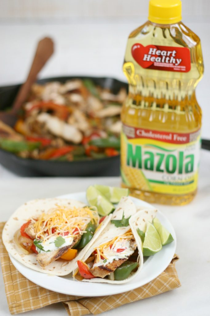Bottle of Mazola oil with finished chicken fajitas on a white ceramic plate