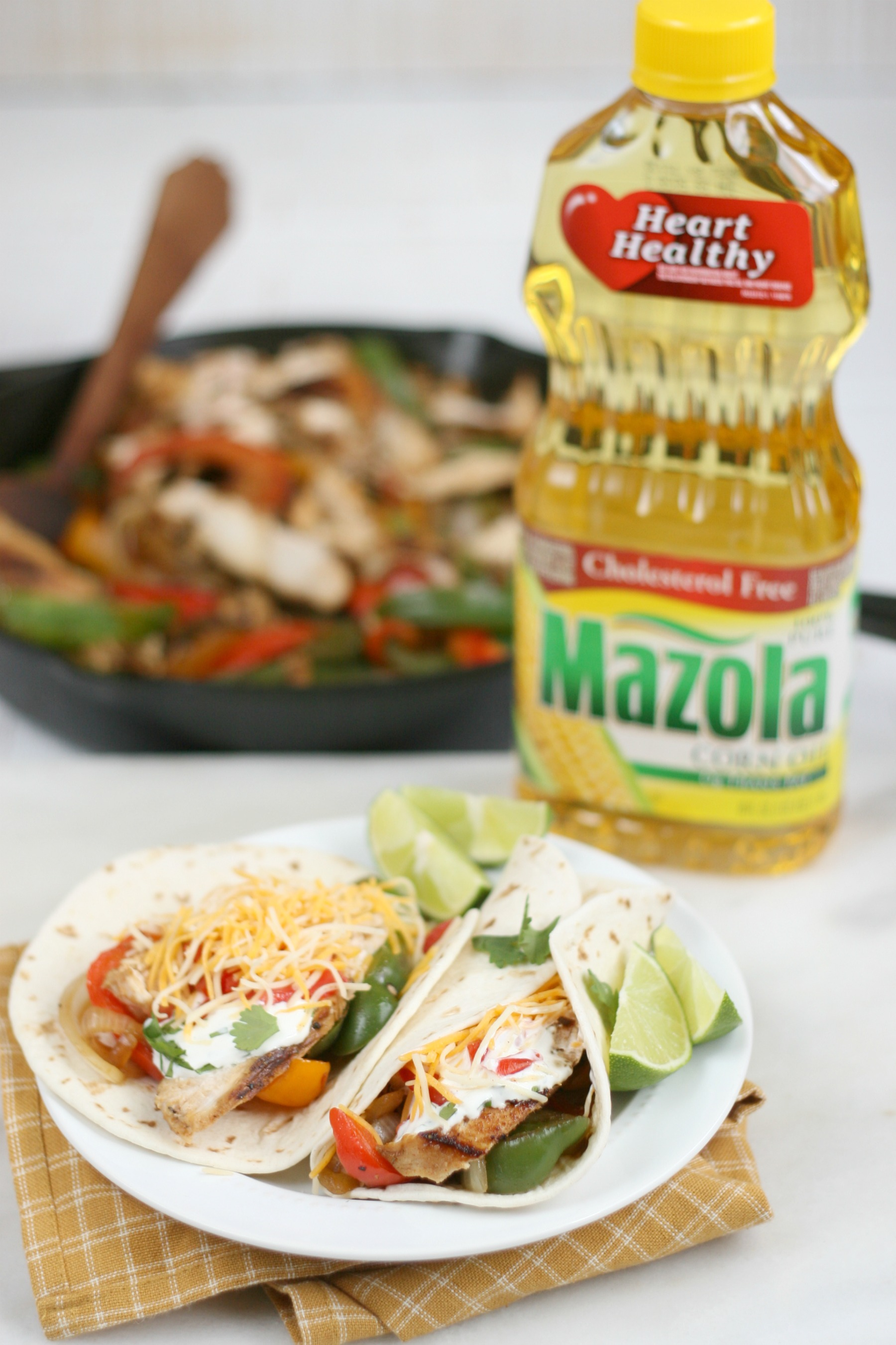 Bottle of Mazola oil with finished chicken fajitas on a white ceramic plate.