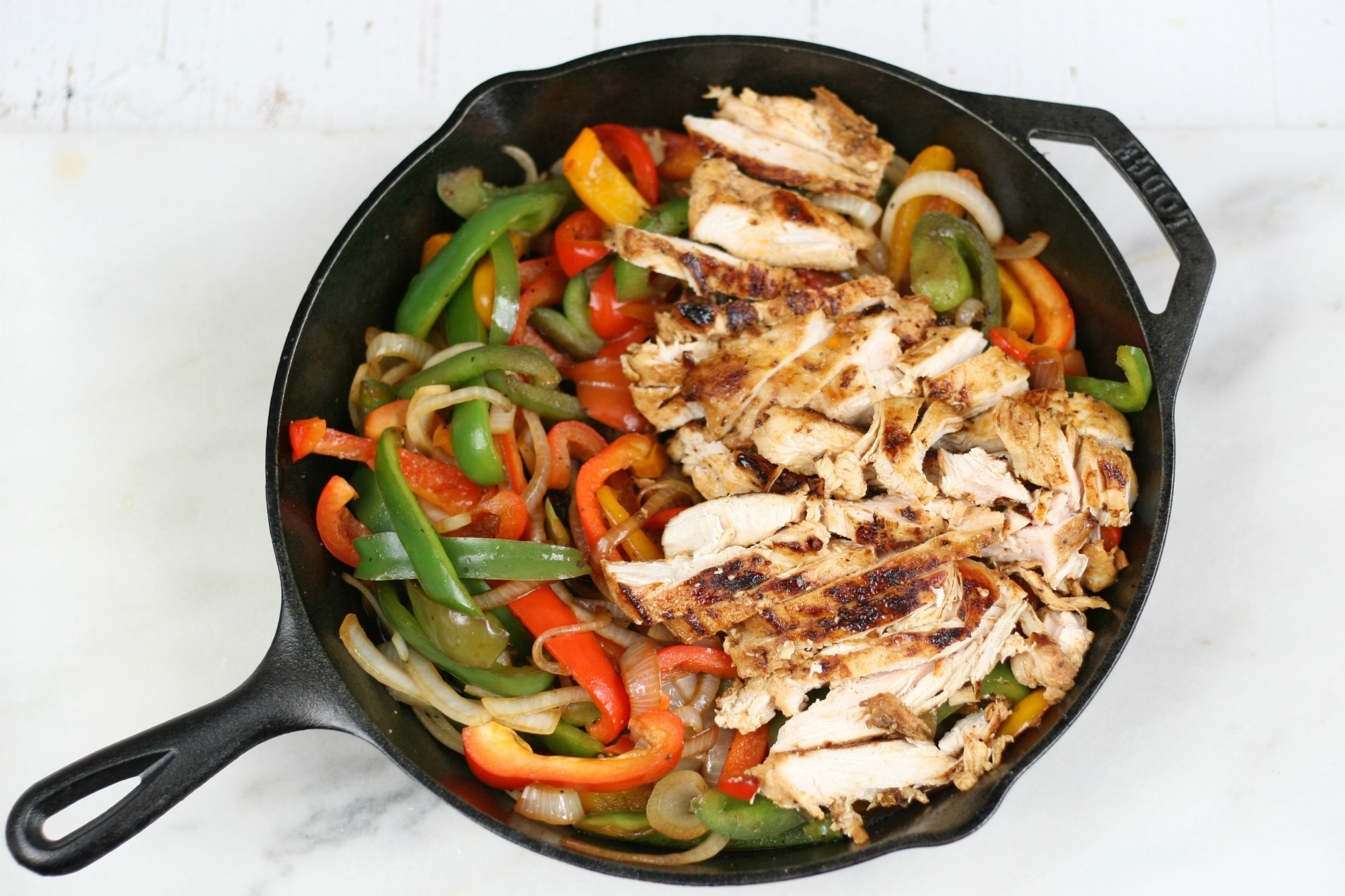 grilled chicken and sautéed onions and multi colored bell peppers in a cast iron skillet.