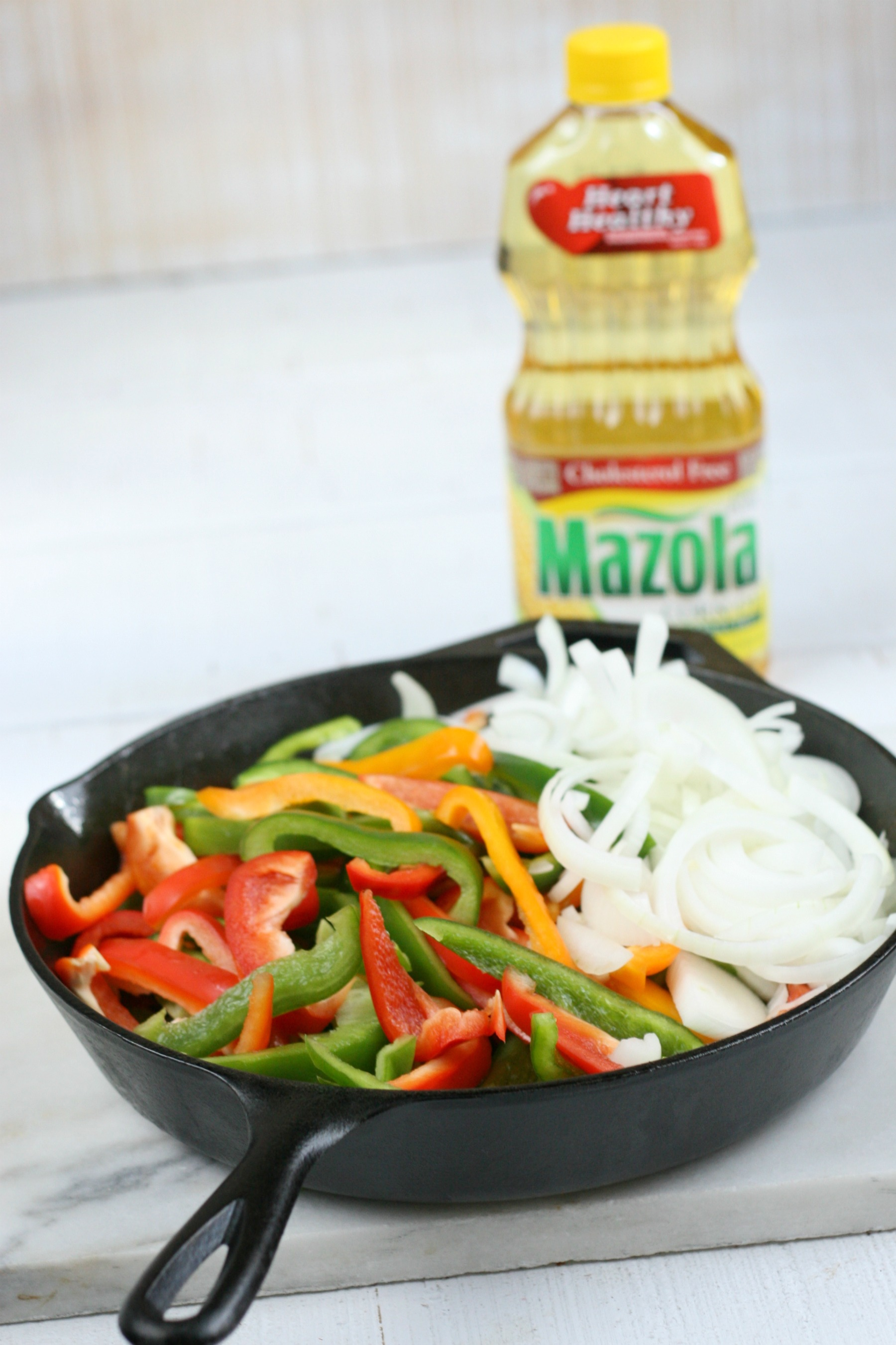 Bottle of Mazola corn oil behind a cast iron skillet of onions and peppers.