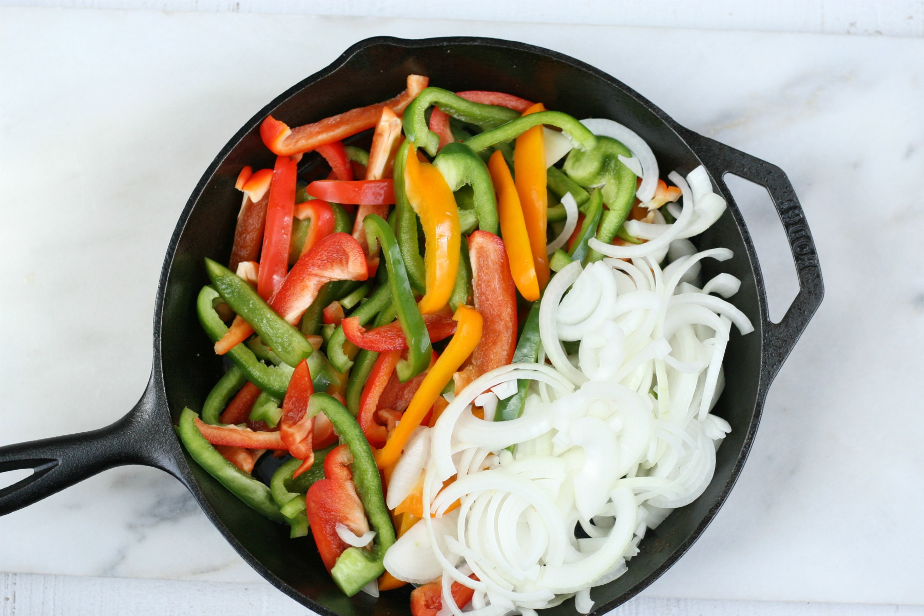 cut up bell peppers and white onions in a cast iron skillet.