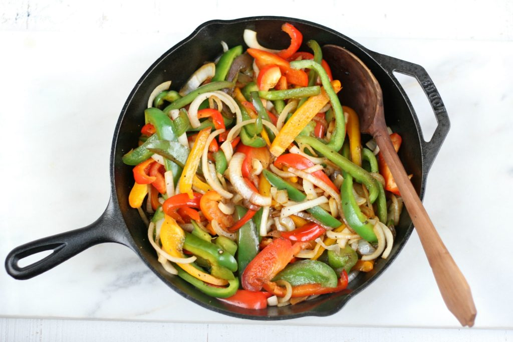 sauteed onions and peppers in a cast iron skillet and hand carved wooden spoon