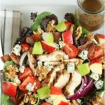 garden salad with chunks of apples, blue cheese, red onion slices, grilled chicken, and walnuts