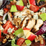 garden salad topped with grilled chicken, chunks of blue cheese, sliced red onion, walnuts, and red and green apples