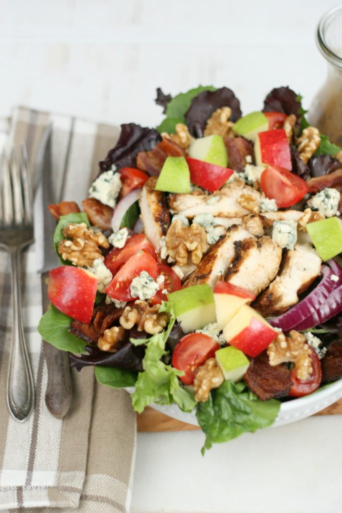 Harvest chicken salad with mixed baby greens, slices of red onions, walnuts, chunks of blue cheese, red and green apple chunks