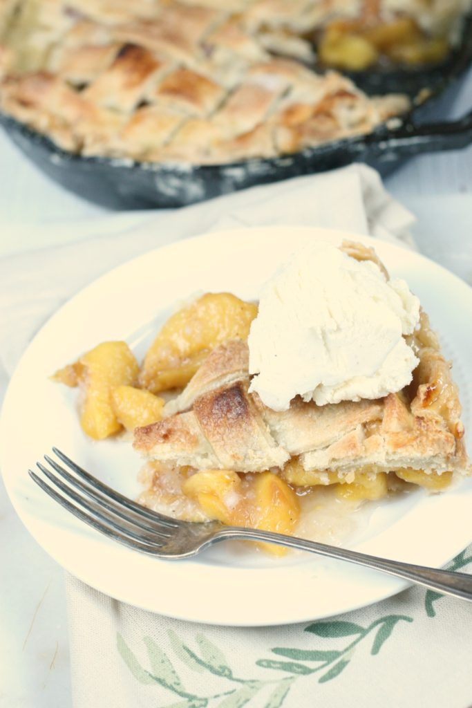 slice of homemade peach pie with vanilla ice cream on top. Fork on the laying to the side of the pie on a white glass plate