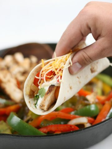 Chicken fajitas with onions and peppers being hand held