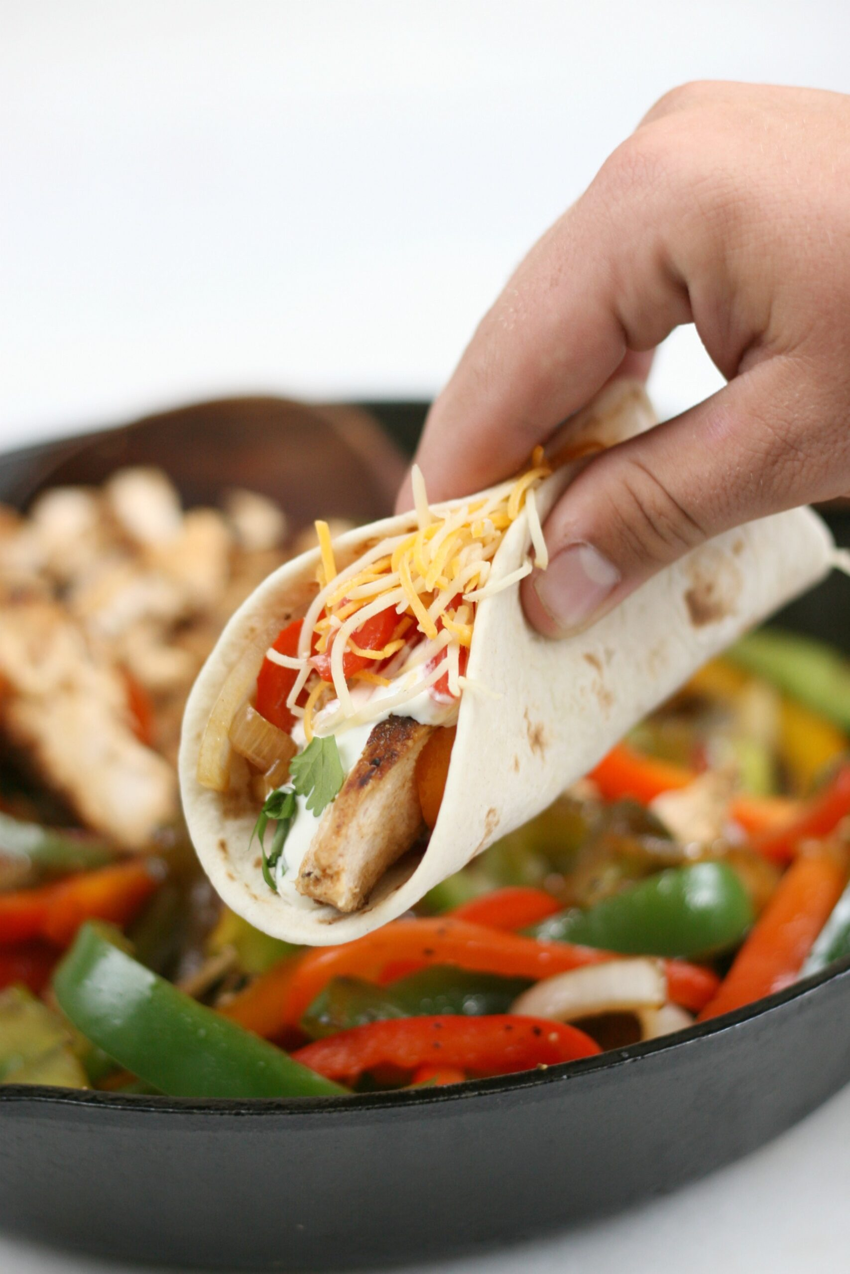 Chicken fajitas with onions and peppers being hand held.