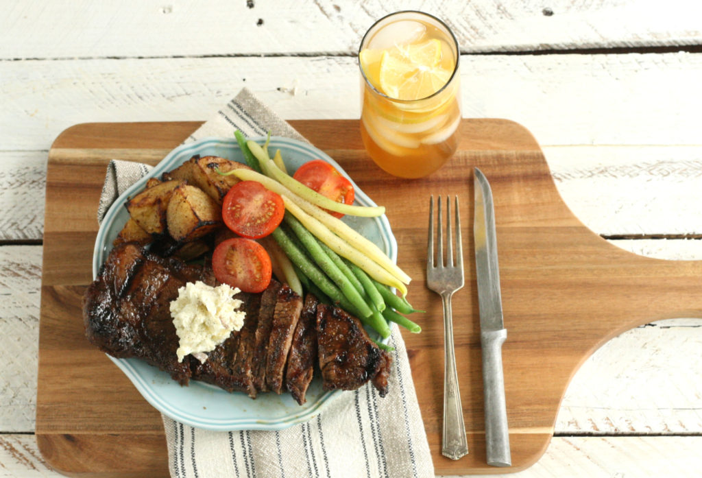 Whiskey Marinated Steak on a cutting board with sliced tomatoes, grilled potatoes, and freshly picked green beans, sitting on a plate on top of a wooden cutting board with handle