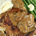 pan seared pork chops on a white plate with mushroom sauce, mashed potatoes, and fresh green beans