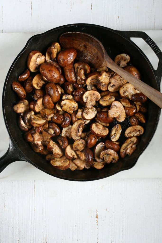 mushrooms sauteed in cast iron skillet with hand carved wooden spoon