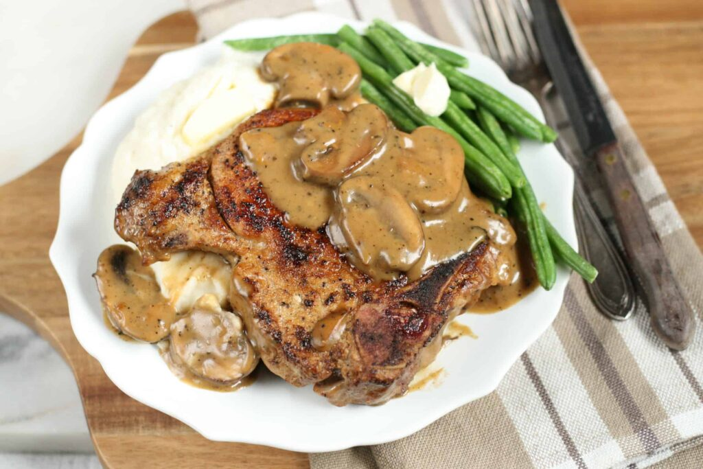 cast iron pork chops with a mushroom cream sauce and mashed potatoes on a white plate