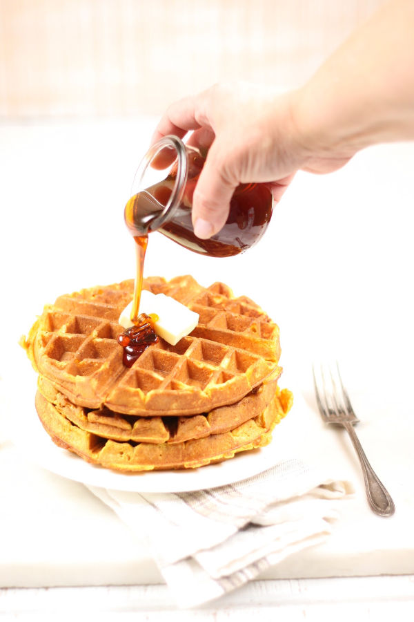 pouring syrup on homemade waffles