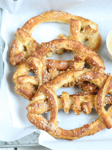 Football shaped soft pretzels with sea salt sitting in a galvanized tray